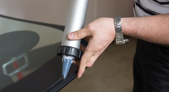 Glazier applying rubber sealing to windshield in garage